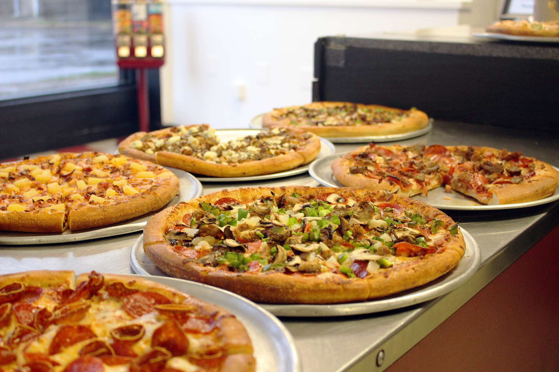 five sloopy's pizzas on a table