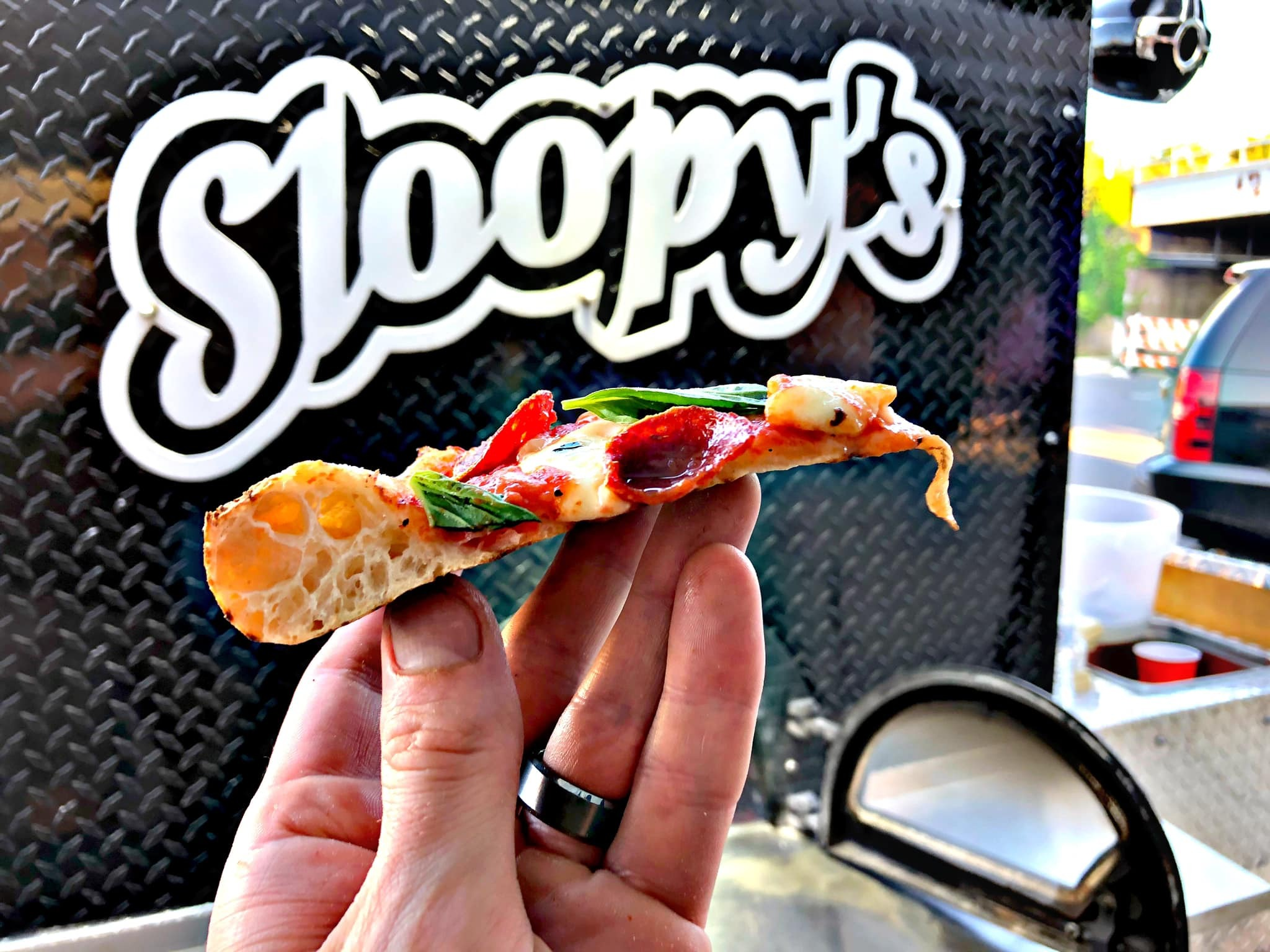 a slice of sloopy's pizza with the mobile pizza oven in the background