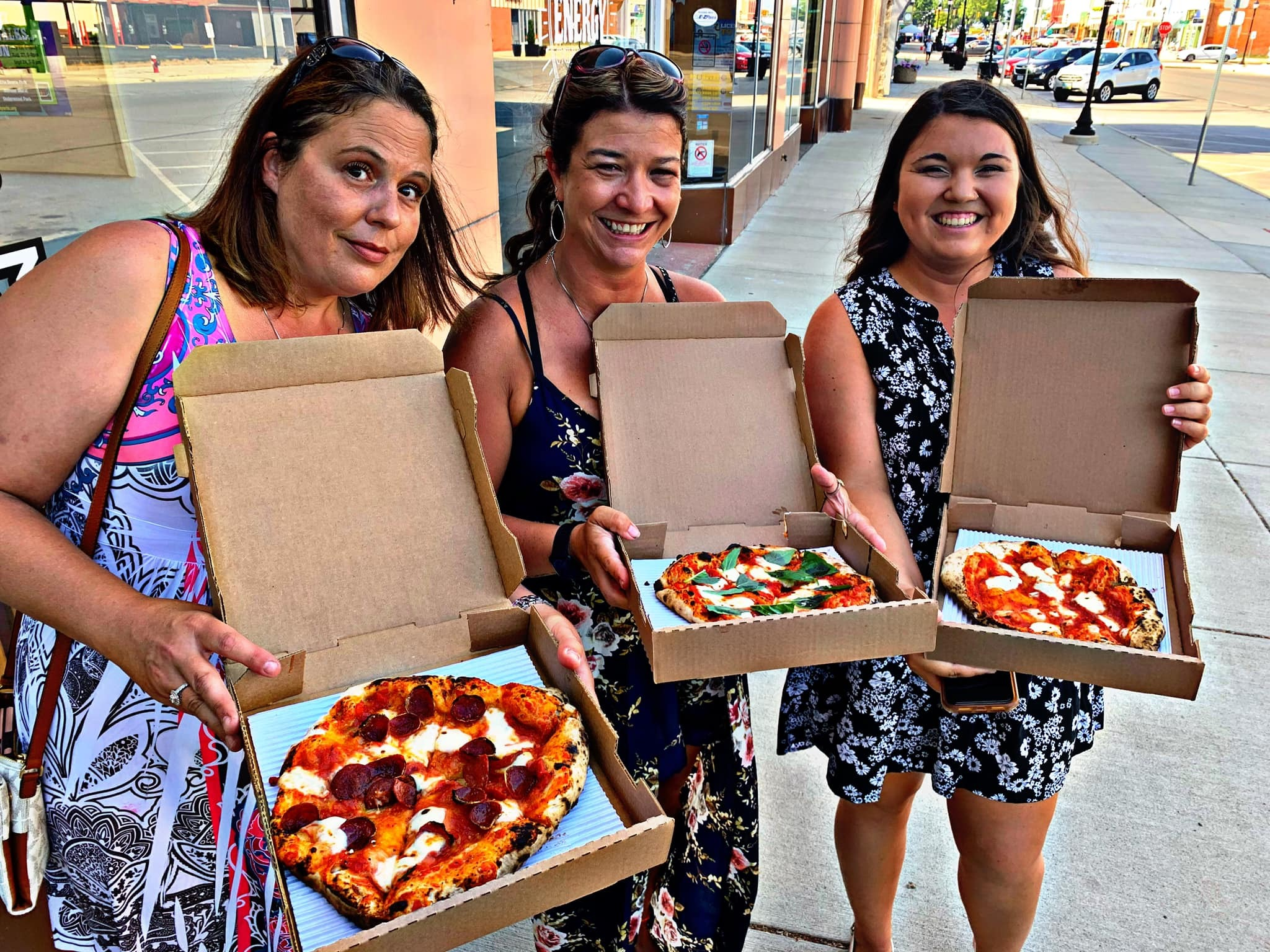three women holding sloopy's pizzas