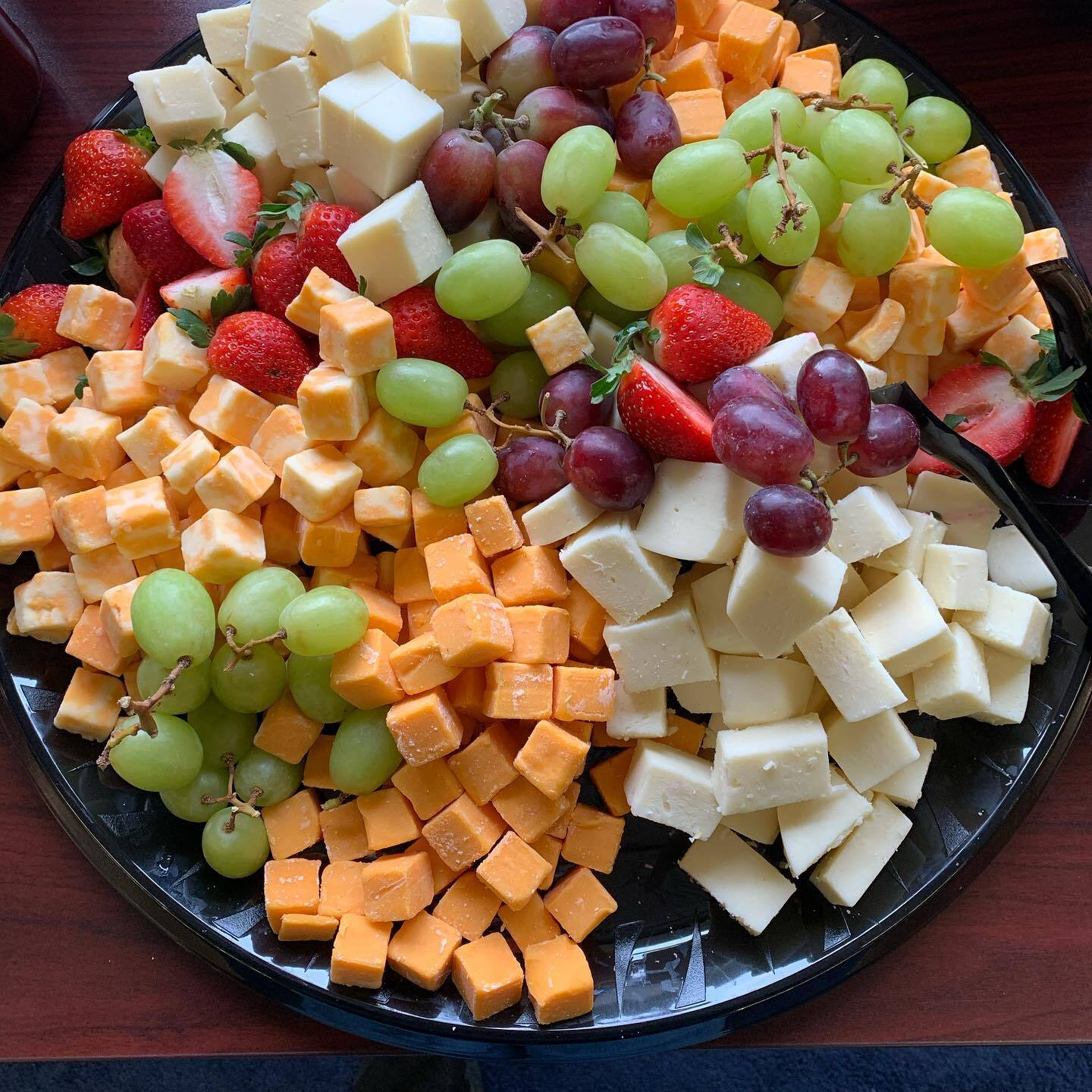 a platter of cheese and fruit