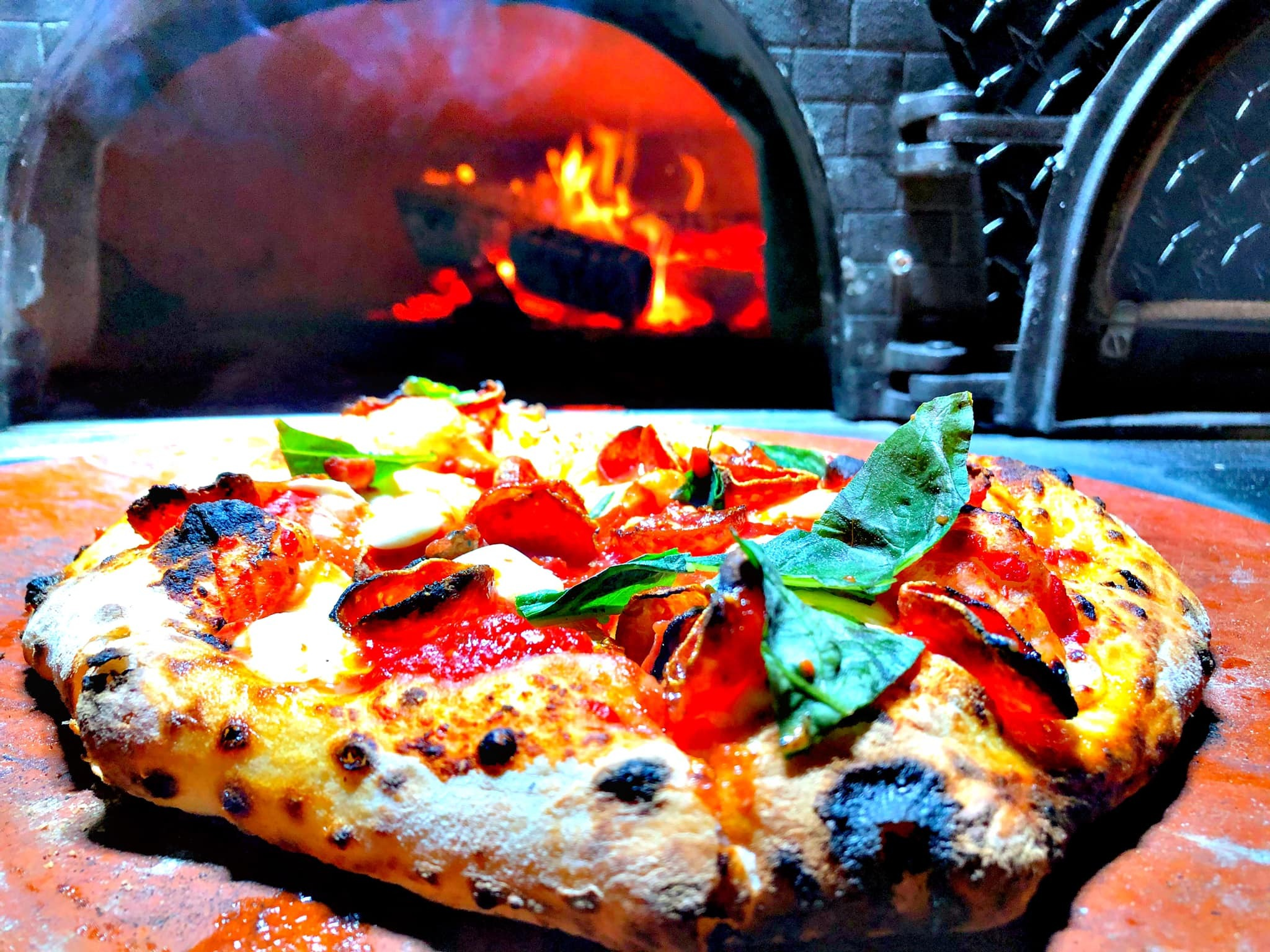 a pizza with a stone oven in the background